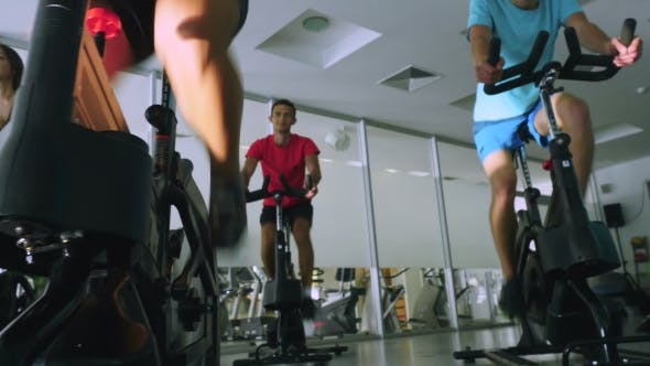 Thumbnail for The Trainer and Young Sportsmen Are Training on the Exercise Bikes in the Gym