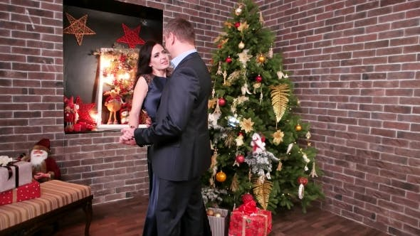 Cover Image for Loving Couple Dancing at a Party, Man Hugging Woman, New Year's Party Near the Christmas Tree, the