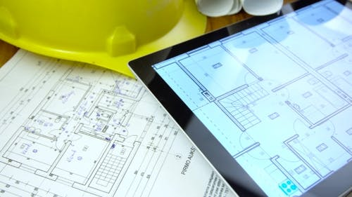Blueprints and Tablet on Table