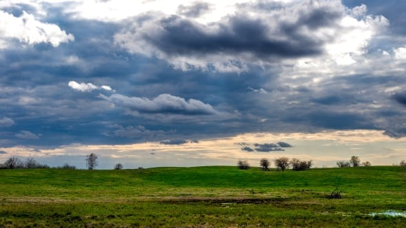 Layers of Clouds Moving Over a Green Field