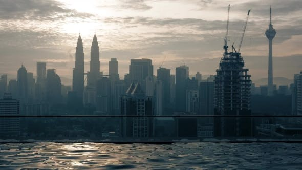 Thumbnail for View of Swimming Pool on the Skyscraper Roof Against Sunrise Building Cityscape. Kuala Lumpur