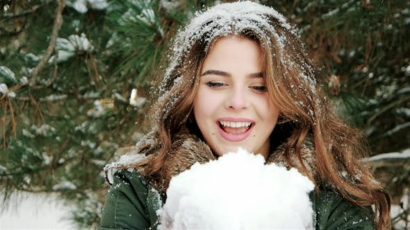 Beautiful Girl Blowing on Snow, Snowflakes Fly