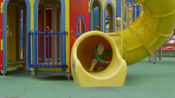 Thumbnail for Active Young Dad Enjoying Playground Slides with Son