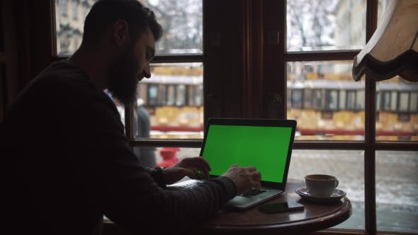 Thumbnail for Man Using Laptop with Green Screen in Cafe