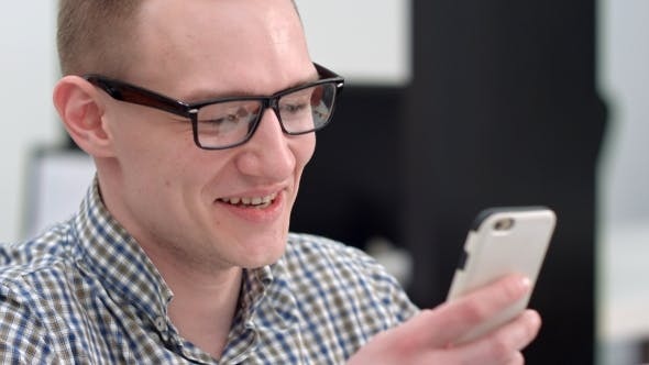 Thumbnail for Young Man in Office Laughing at Text Message on Smartphone