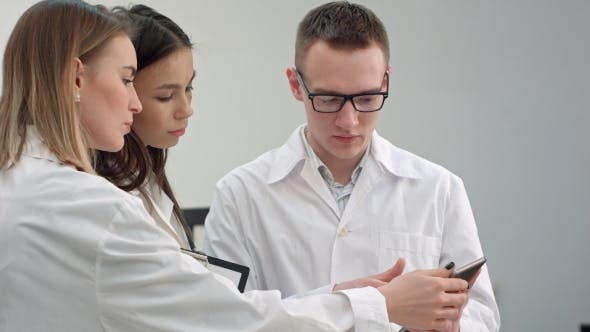 Thumbnail for Female Doctor Showing Something on Tablet To Her Medical Team