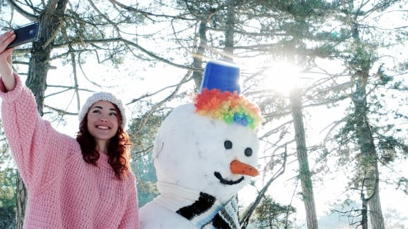 Cover Image for Winter Selfie, Cute Girl Making Photo with Snowman, a Mobile Phone in the Hand of Young Woman Making