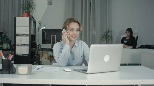 Thumbnail for Two Female Coworkers Working Together Answering Phone Calls in the Office