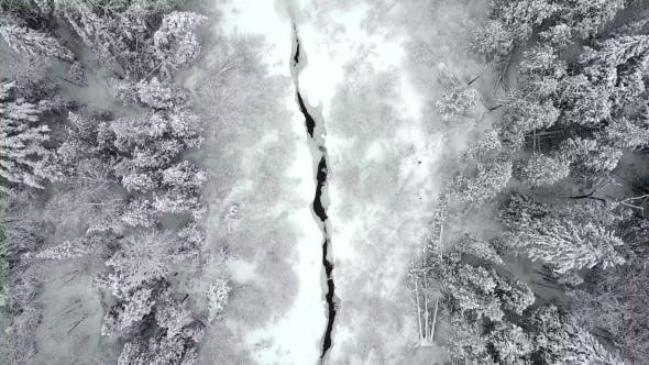 Cover Image for Aerial View Descending Towards a Snow Covered Forest Creek