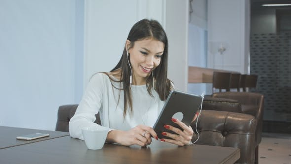 Thumbnail for Beautiful Young Woman Using a Tablet Pc To Make a Video Call While Sitting in a Cafe