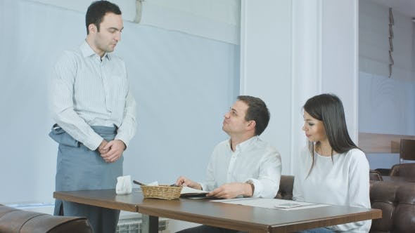 Thumbnail for Waiter Bringing Menu To Young Couple Sitting at the Table in a Restaurant