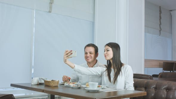 Thumbnail for Happy Young Couple Taking Selfies with Food on Smartphone at a Restaurant
