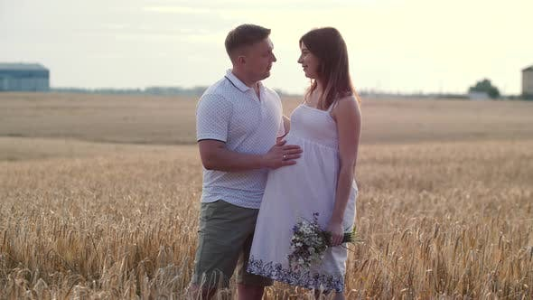 Portrait of Young Pregnant Couple in Field