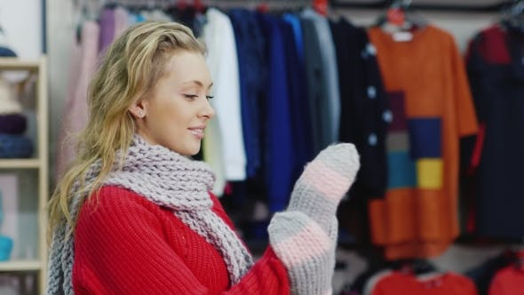 Cover Image for Attractive Woman in a Red Sweater Tries Warm Mittens. It Should Be in a Clothing Store