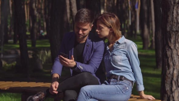 Thumbnail for Couple Sitting on the Bench Use Gadget.