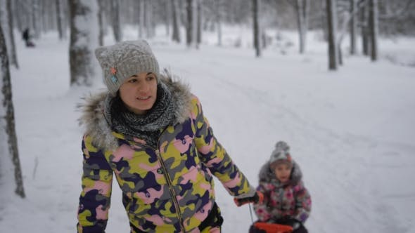 Thumbnail for Mother Ride a Little Girl on a Sled on a Snowy Path in the Park. Cute Women Actively Spends His Free