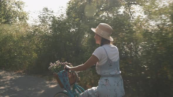 Thumbnail for Dreamy romantic woman rides bicycle in park along river in summer.