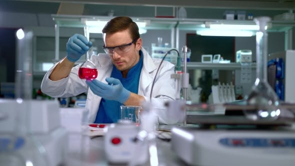 Researcher Analyzing Liquid in Glass Flask and Writing Data at Research Lab
