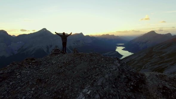 Thumbnail for Woman Celebrating Reaching Peak of a Hike in the Mountains at Sunset