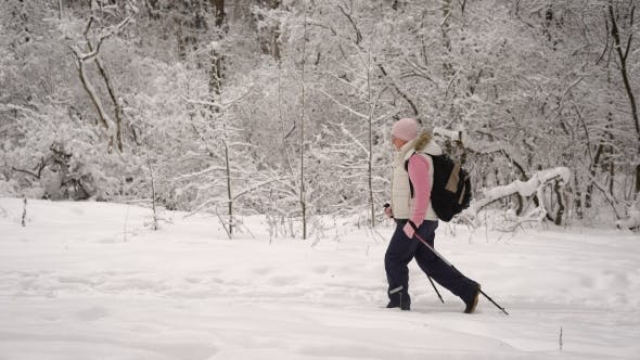 Thumbnail for Active Woman Dressed in Warm White Waistcoat and Black Trousers Doing Nordic Walking
