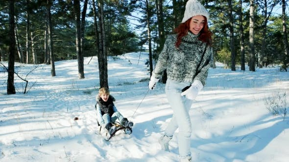 Thumbnail for Sledding in the Forest, Mom Rolls Her Son on a Sled, Happy Family in the Winter, Fun Entertainment