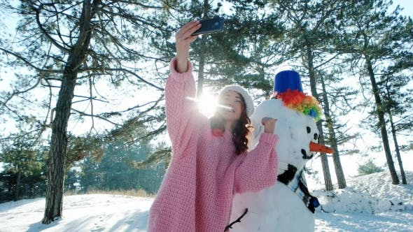 Thumbnail for Fun Selfie Photo in Winter Forest Backlit, Cute Girl Making Photo with a Snowman, Winter Selfie
