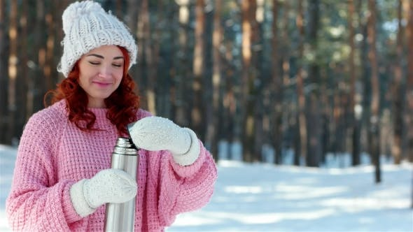 Cover Image for Girl Pours Hot Drink From a Metal Thermos, Thermos in Hands , Hand Pours Tea Into a Cup,