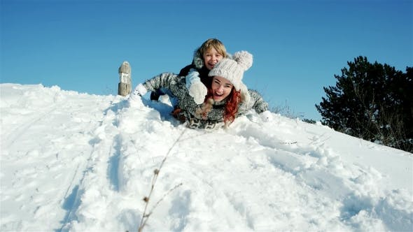 Thumbnail for Family Sleigh Ride Through the Snow, Happy Mother and Son Moves Down on a Sled, Sledding Down the
