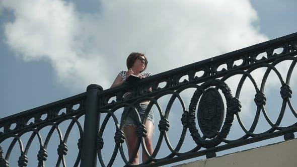 Happy Girl with Sunglasses On a Bridge