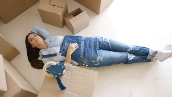 Thumbnail for Young Woman Relaxing on the Floor After Packing