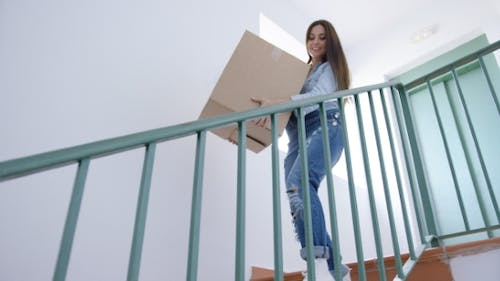Young Woman Carrying a Carton Downstairs