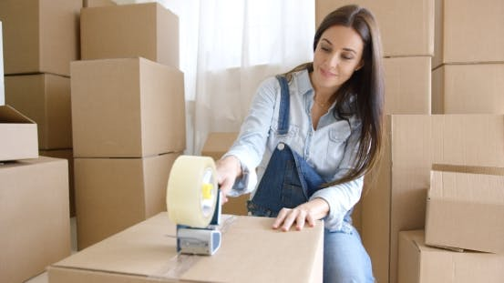 Cover Image for Young Woman Moving Home Packing Boxes