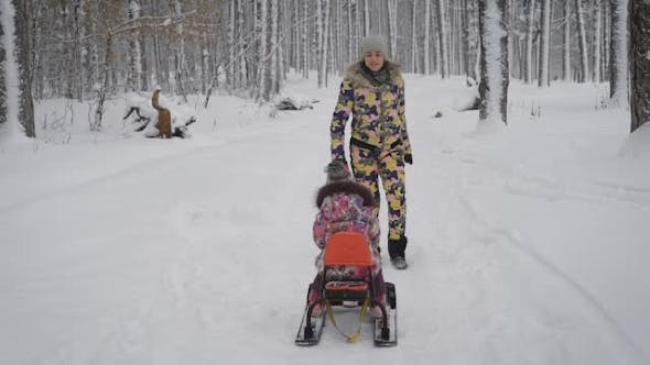 Young Mum Rolls on a Sled