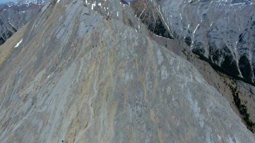 Aerial: Orbit Around Hikers Preparing To Follow Steep Mountain Ridgeline