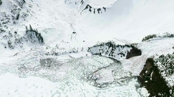 Thumbnail for Aerial: Tilting Down Over Avalanche Debris Flowing Into Frozen Lake