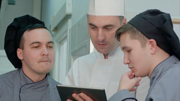 Thumbnail for Konzentrierter Chef zeigt seinen Auszubildenden etwas auf dem digitalen Tablet