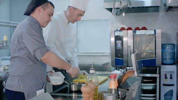 Thumbnail for Küchenchef Knoblauch auf dem Schneidebrett mit einem Messer schneiden und mit Salz mischen, das von einem anderen gebracht wird