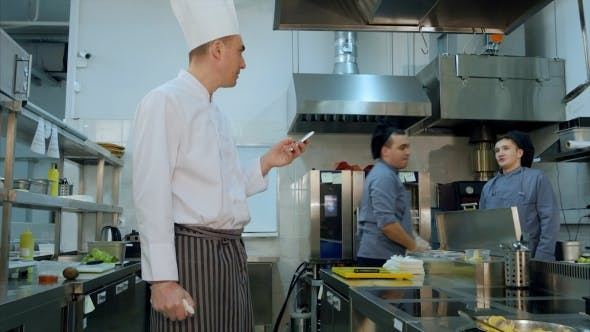 Thumbnail for Chef Reading Something From His Phone and Talking To One of the Cook Trainees