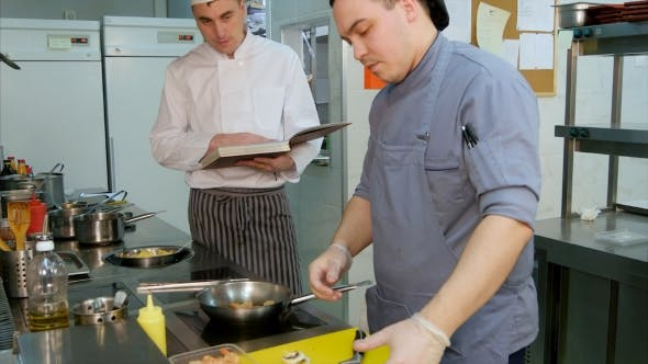 Thumbnail for Chef with Recipe Book Watching Young Cook Preparing Dish in the Kitchen