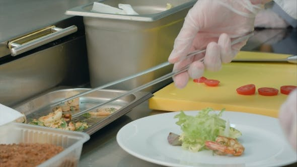 Thumbnail for Chef's Hands Decorating Shrimp Salad on a White Plate