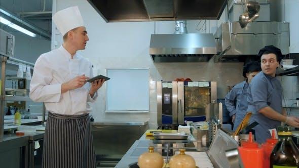Thumbnail for Chef mit digitalem Tablet und beobachten seine Auszubildenden kochen