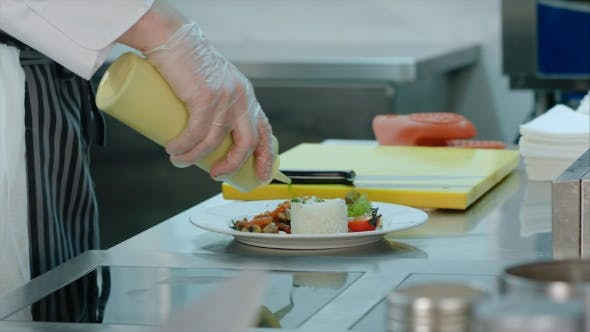 Thumbnail for Chef's Hands Adding Sauce To the Rice with Vegetables on a Plate