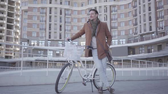 Thumbnail for Handsome Serious Man in Brown Coat and Light Blue Jeans Standing with His Bicycle in the City in