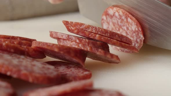 Thumbnail for Cured sausage of air-dried meat cutting 4K 2160p 30fps UltraHD footage - Salami cut on smaller piece