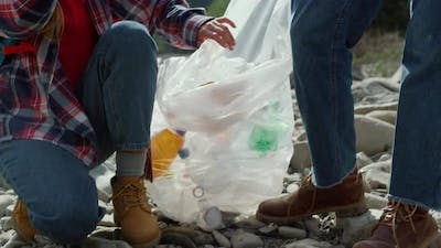 Couple Collecting Bottles Into Bag