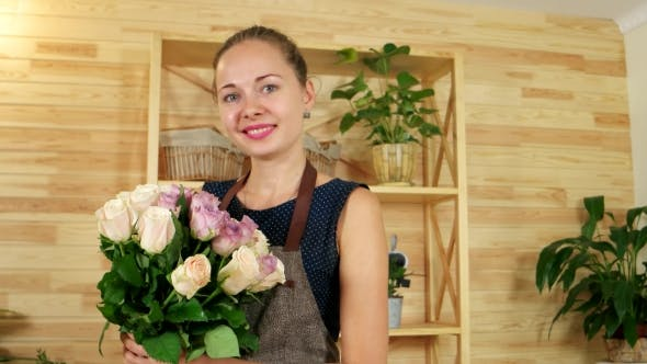 Cover Image for Cute Girl with a Bouquet in Hands, Florist Working in a Flower Shop, Golan Roses on the Counter for