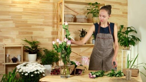 Cover Image for Beautiful Girl Florist, Salesman in a Flower Shop, She Unpacks Roses, Preparing Flowers for Making