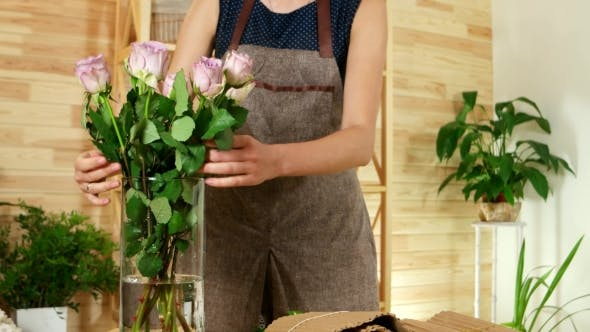 Thumbnail for Girl in a Flower Shop, Florist Puts a Rose in a Glass Vase with Water, Beautiful Fresh Flowers Is a