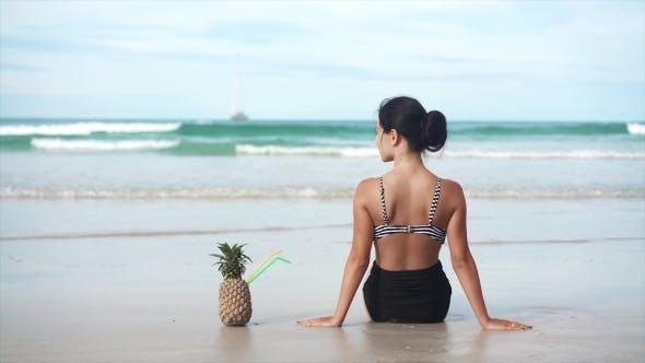 Thumbnail for Mädchen sitzend mit Ananas auf dem Strand in der Nähe Meer