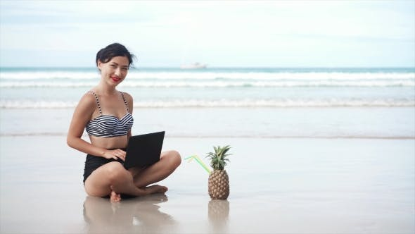 Thumbnail for Young Girl Using Laptop on the Beach